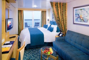 Onboard, on board stateroom, Outside oceanview or ocean view stateroom, category E1, balcony, with blue couch and bowl of fruit on glass table. View of balcony with 2 deck chairs, Freedom class, new bedding, Freedom of the Seas, Freedom class, FR